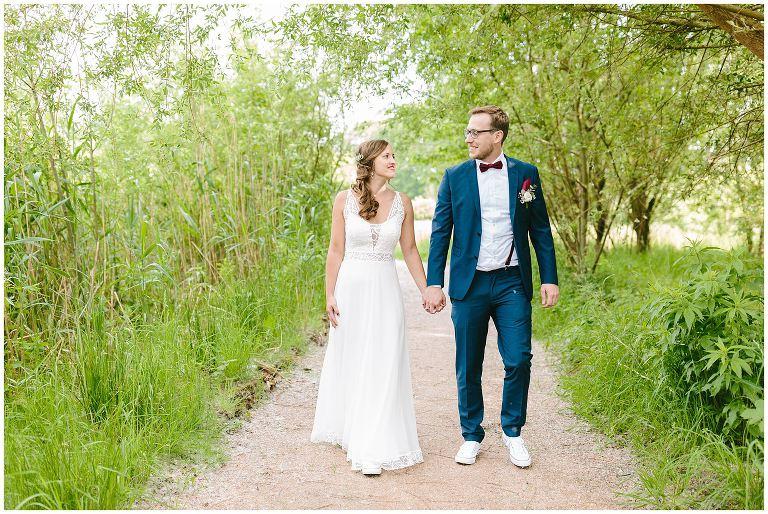 Brautpaar geht Hand in Hand in den Rieselfeldern in Münster - Hochzeitsfotograf Lotharinger Kloster