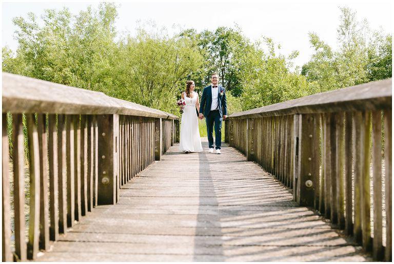 Brautpaar auf einer Brücke in den Rieselfeldern in Münster - Hochzeitsfotograf Lotharinger Kloster