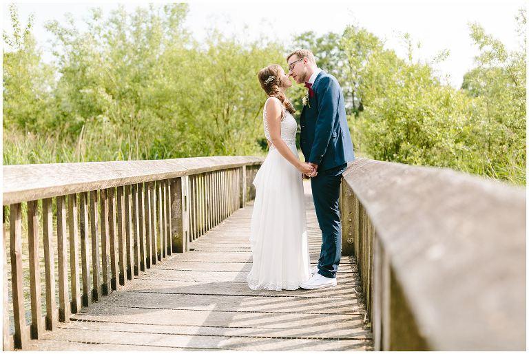 Brautpaar küsst sich auf einer Brücke in den Rieselfeldern - Hochzeitsfotograf Lotharinger Kloster