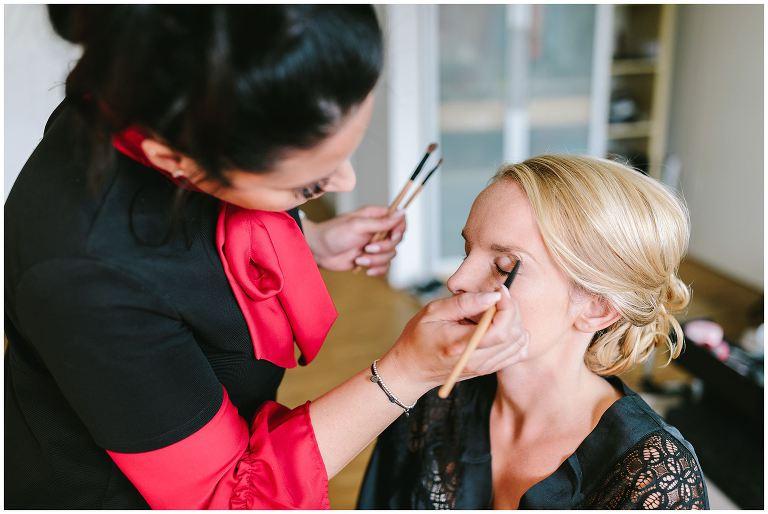 Stylistin schminkt die Augen der Braut während der Brautwerdung in Münster