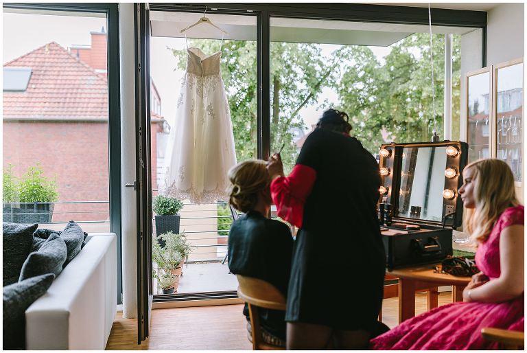 Brautkleid hängt im Fenster vor der braut beim Styling