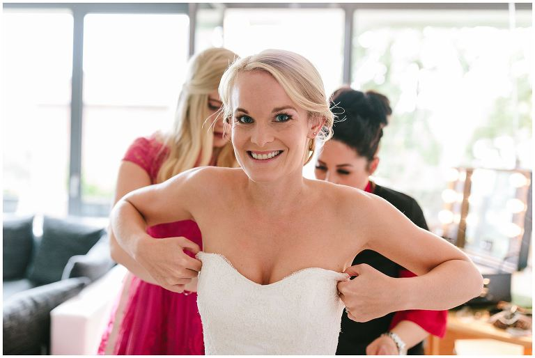 Braut beim Anziehen des Brautkleids