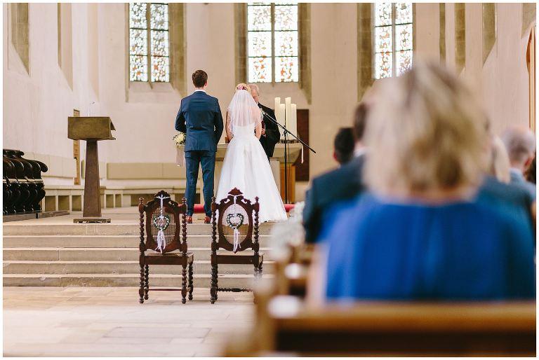 Brautpaar steht vor dem Pfarrer kurz vor der Trauung