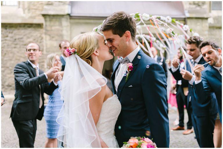 Brautpaar küsst sich nach der Trauung vor der Kirche