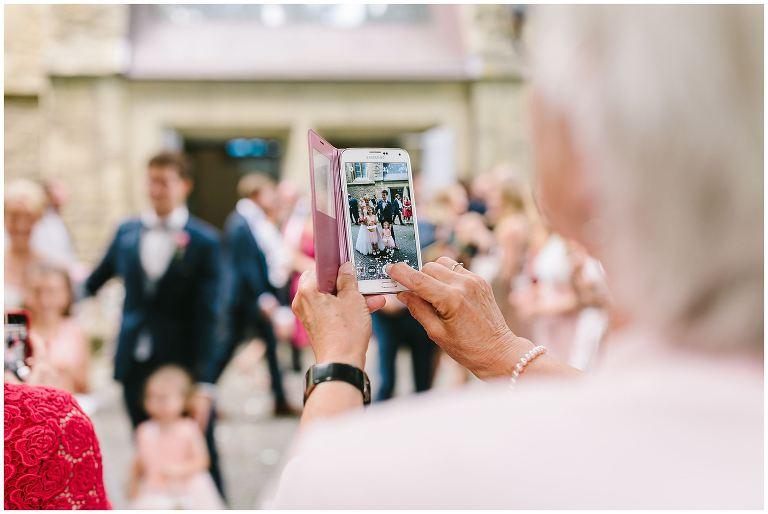 Hochzeitsgast macht mit dem Handy ein Bild vom Brautpaar