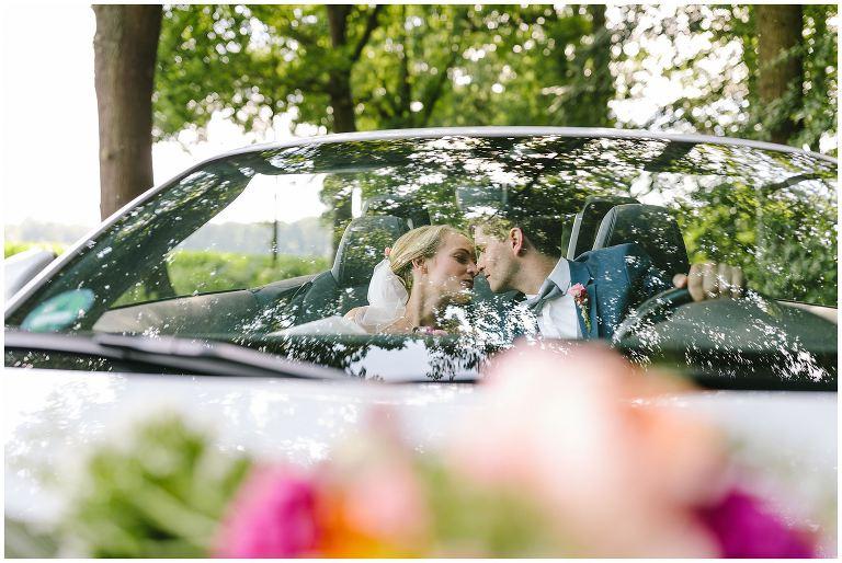 Brautpaar küsst sich im Auto