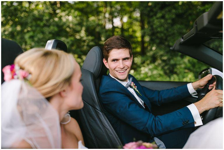 Bräutigam schaut seine Braut im Auto an