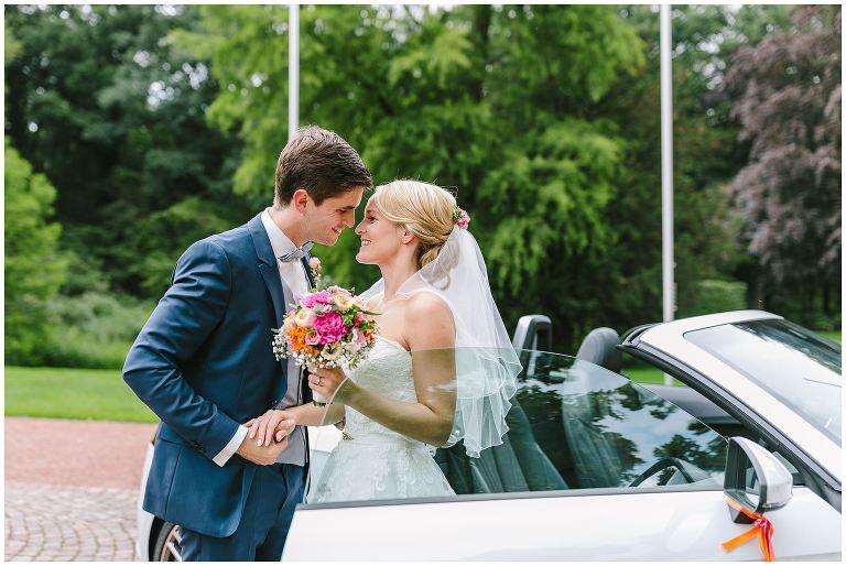 Bräutigam hilft seiner Braut aus dem Brautauto am Gut Havichhorst