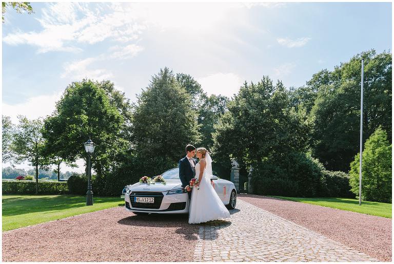 Brautpaar vor dem Brautauto am Gut Havichhorst