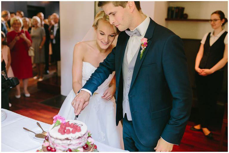 Brautpaar schneidet Hochzeitstorte an auf dem gut Havichhorst