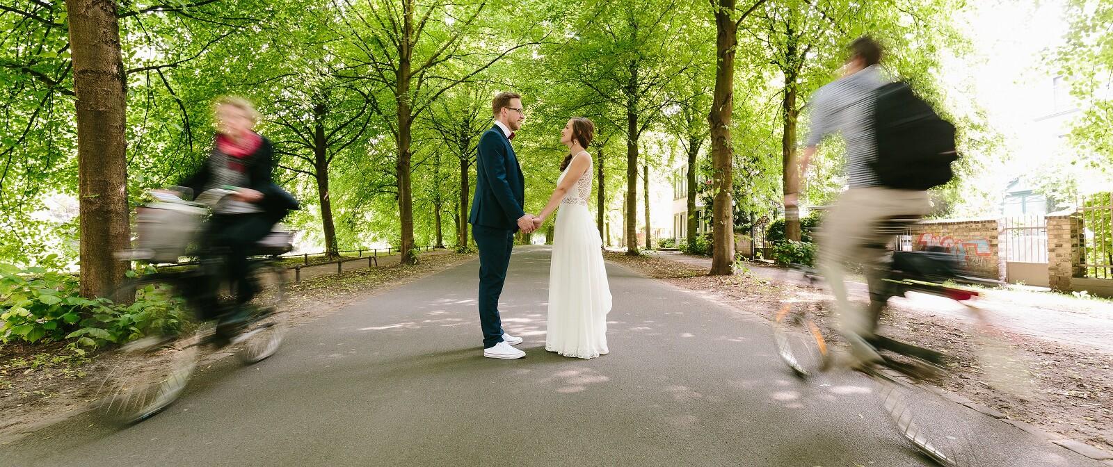Hochzeitspaar mit zwei Fahrradfahrern auf der Promenade in Münster
