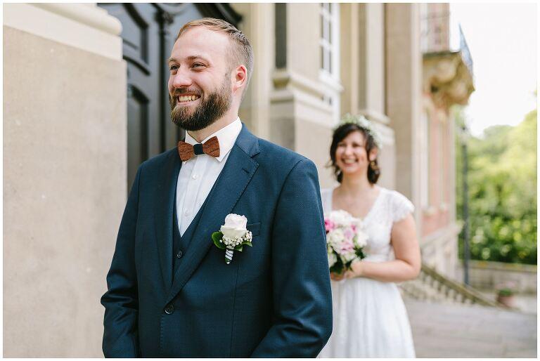 Firstlook vom lachenden Bräutigam und seiner Braut