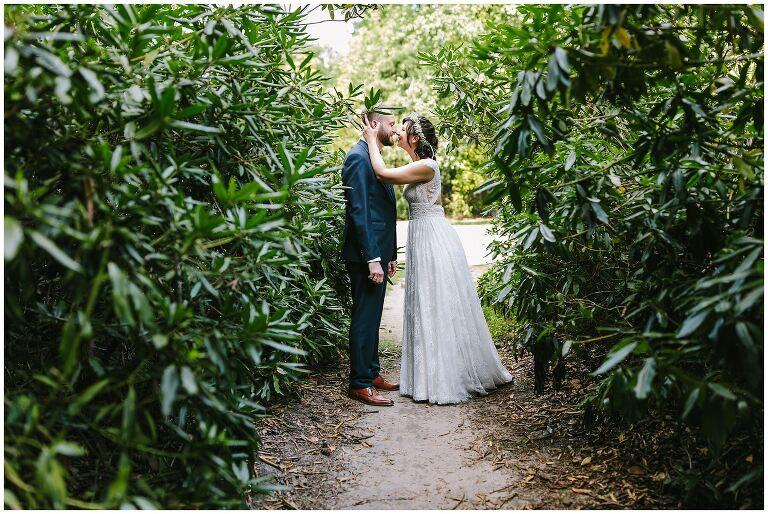 Braut und Bräutigam küssen sich im Park