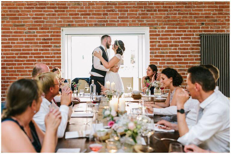 Brautpaar küsst sich auf der Hochzeitsfeier