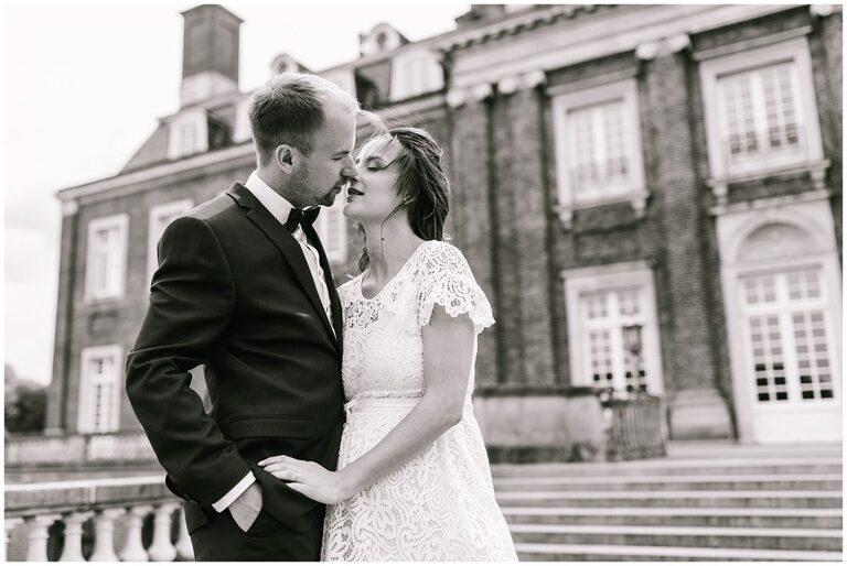 Brautpaar küsst sich auf einer Treppe vor dem Schloss