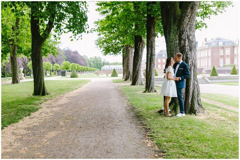 Brautpaar im Schlossgarten vor einem Baum