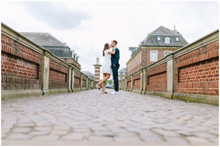 Brautpaar küsst sich auf einer Brücke
