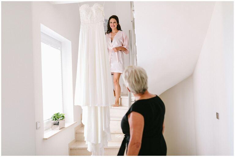 Braut kommt die Trepper herunter und schaut auf das Brautkleid