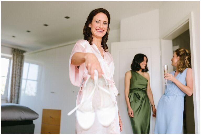 Braut strahlt und zeigt ihre Brautschuhe