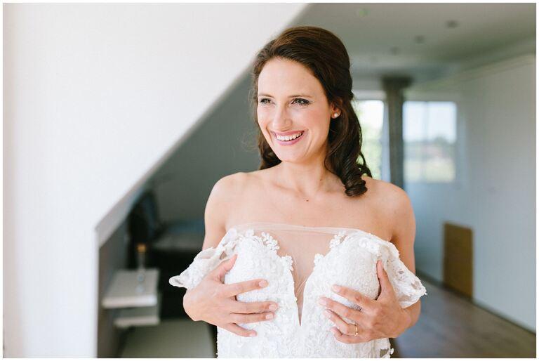 Braut zieht Ihr Brautkleid an und strahlt
