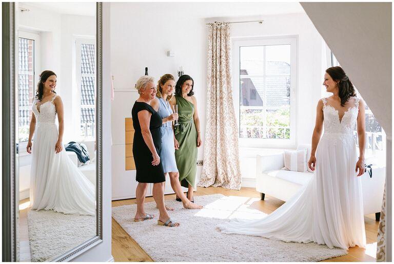 Braut im Brautkleid vor einem Spiegel wird von Freundinnen bestaunt