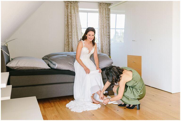 Braut bekommt von der Trauzeugin die Schuhe angezogen