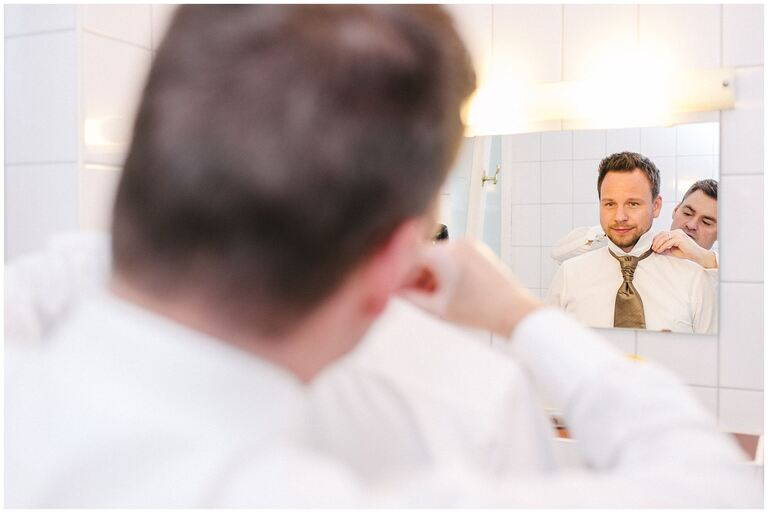 Trauzeuge hilft Bräutigam vor dem Spiegel beim Ankleiden