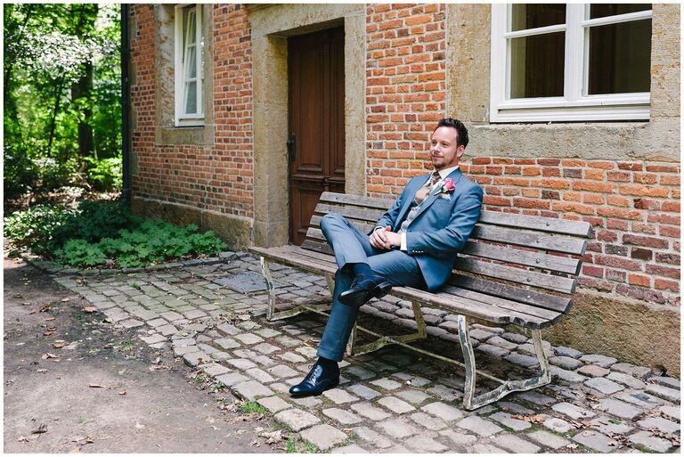 Bräutigam sitzt auf einer Bank