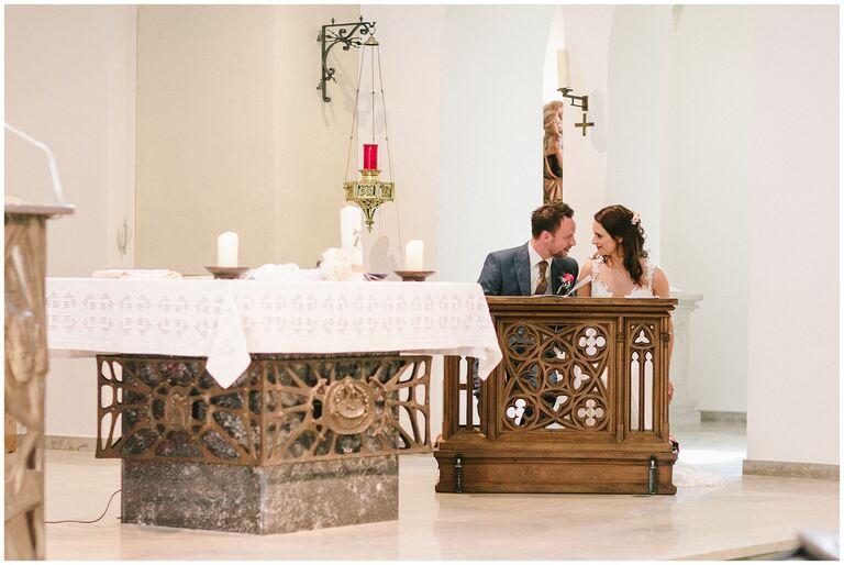Braut und Bräutigam schauen sich in die Augen vor dem Altar