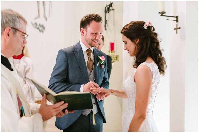 Bräutigam steckt seiner Braut den Ring an