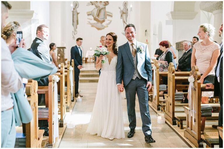 Brautpaar verlassen gemeinsam die Kirche nach der Trauung