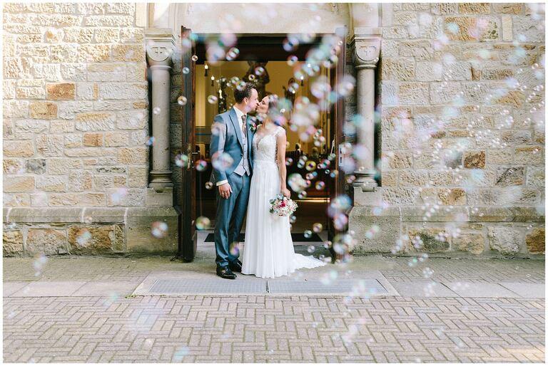 Brautpaar küsst sich im Kirchenportal