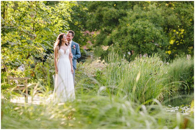 Braut steht hinter seiner Braut und schaut sie verliebt an