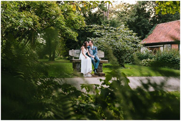 Brautpaar sitzt auf einer Parkbank und küsst sich