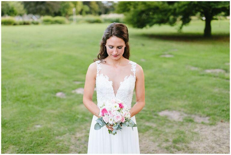 Braut schaut auf den Brautstrauß