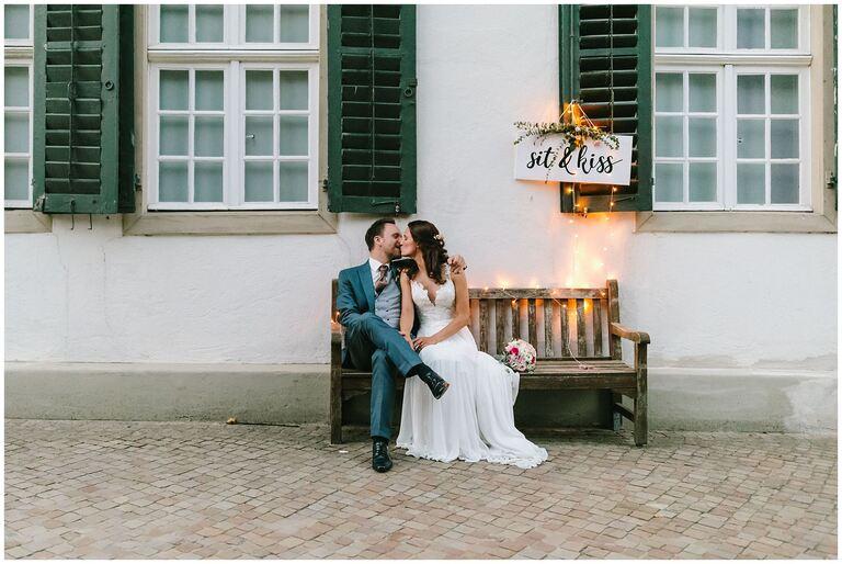 Brautpaar sitzt auf einer Bank und küsst sich im Salinenpark Rheine