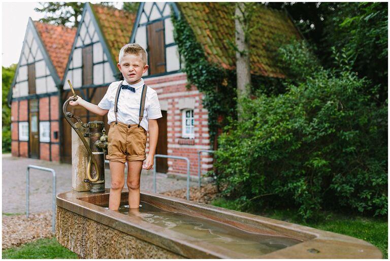 Kleiner Junge spielt mit Wasser im Salinenpark Rheine