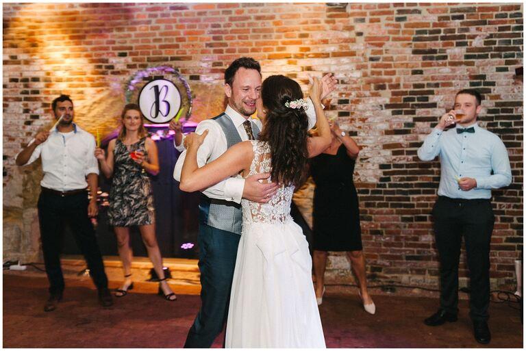 Bräutigam schaut Braut verliebt beim Tanzen an