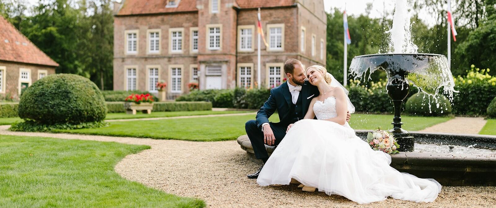 Hochzeitspaar im Park vor einem Springbrunnen